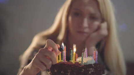 Lonely woman lighting candles on her birthday cake