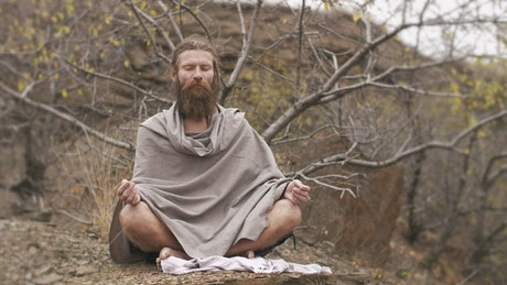 Long beard man meditating in the forest