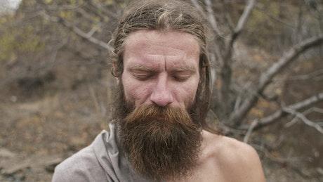 Long beard man waking up from meditation