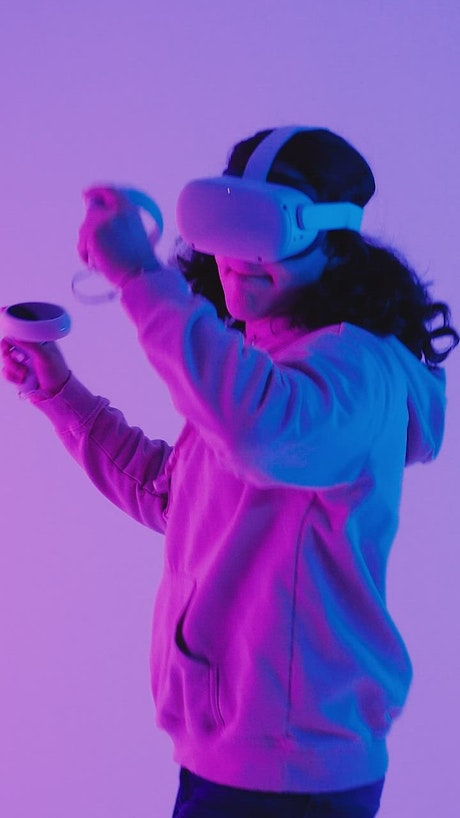Long-haired boy playing VR video games