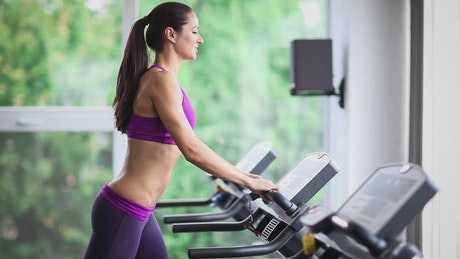 Long-haired sport woman running on treadmill at gym