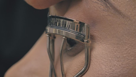 Look of a woman with an eyelash curler