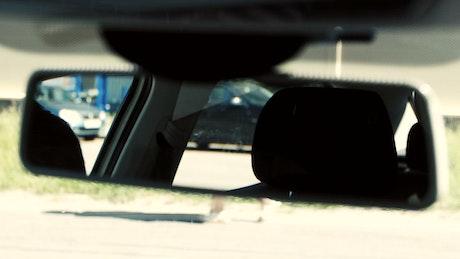 Looking in a car mirror