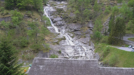 Low view of a waterfall on a forested mountain