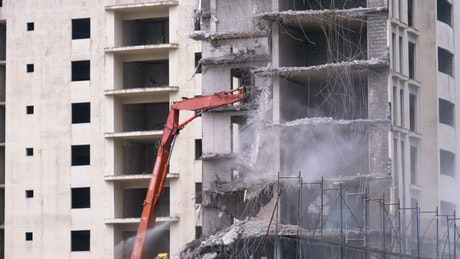 Machine cranes destroying a concrete building