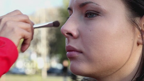 Make-up artist applying makeup outdoors