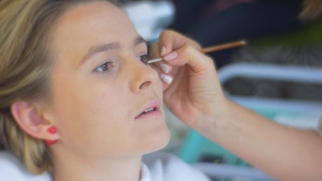 Makeup artist applying eye makeup to a woman