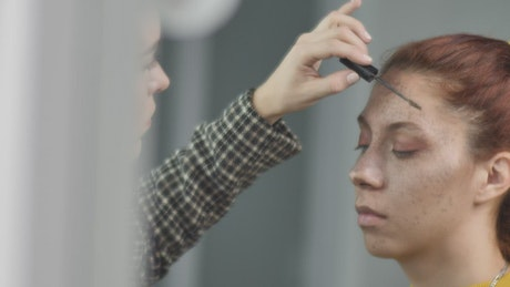 Makeup artist putting makeup on the eyebrows of a young model
