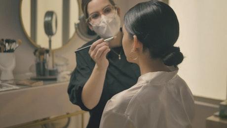 Makeup artist working in her beauty salon