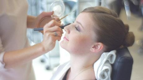 Makeup artist working on bride's face