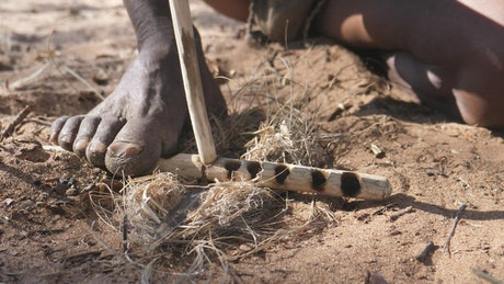 Making fire with wooden sticks on the ground