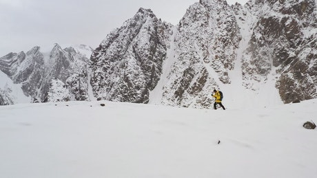 Male climber walking through the snow in the mountains