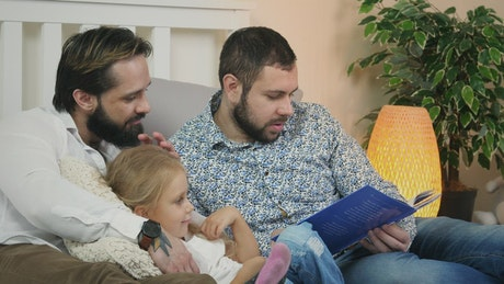 Male couple reading a story to a child