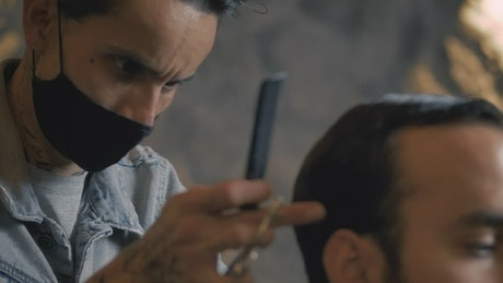 Male hairstylist cutting a client's hair