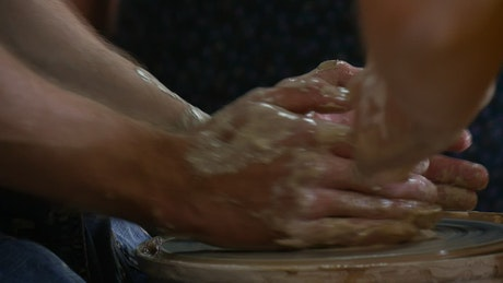 Male hands working on wet clay