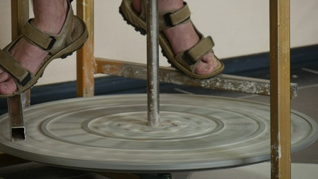 Male potter feet in sandals and rotating wheel