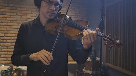 Male violinist recording in a studio