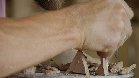 Male working on clay with cutting tools