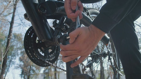 Man adjusting the pedals of his bicycle