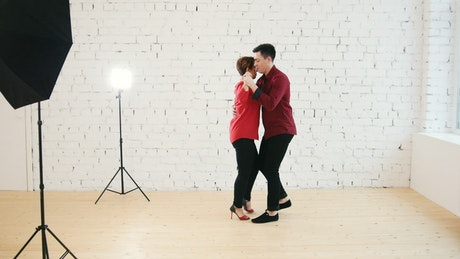Man and woman dancing in a white room