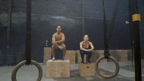Man and woman doing box jump