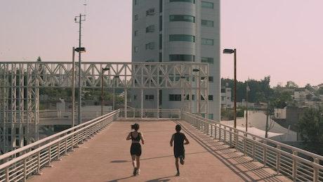 Man and woman exercising on a pedestrian bridge