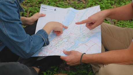 Man and woman in nature analyzing a map together