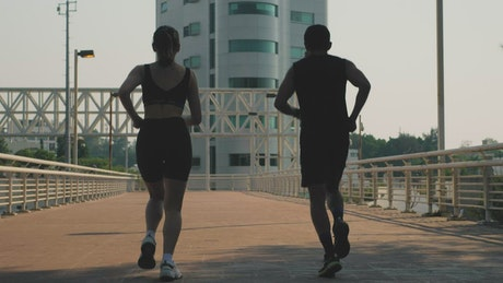 Man and woman jogging together on the street