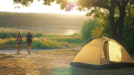 Man and woman returning to their camp in nature