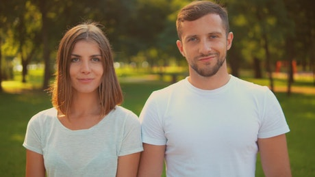 Man and woman smiling head-on in a park
