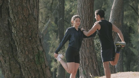 Man and woman stretching in a forest prior to exercise