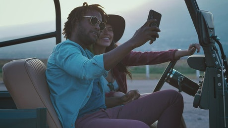 Man and woman taking selfies during a road trip