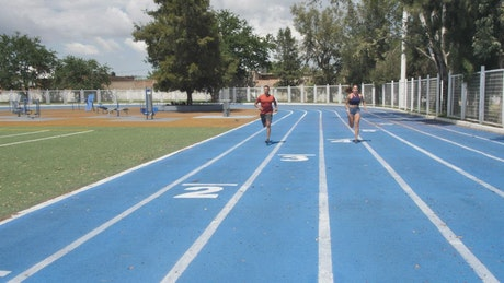 Man and woman training on a running track