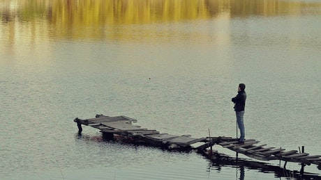 Man appreciating a lake on a worn and broken pier