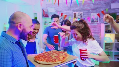 Man brining a pizza to a party