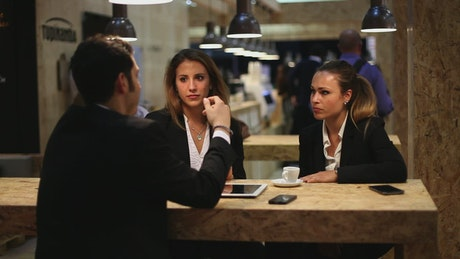 Man chatting with two women in a cafe