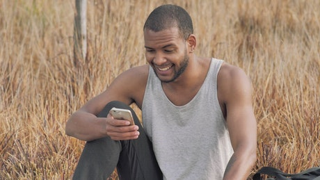 Man checks his smartphone after training