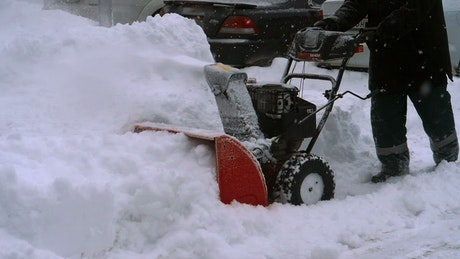 Man clearing snow with a snow blowing machine