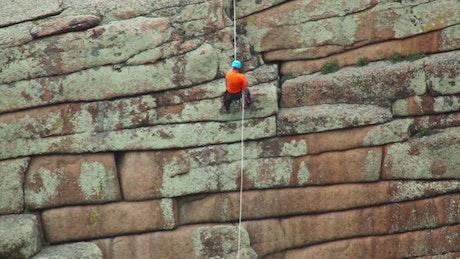 Man climbing down a rock