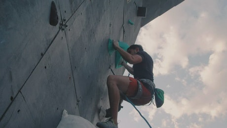 Man climbing to the top of a mountaineering wall