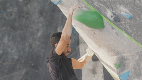 Man climbing up a sloping mountaineering wall