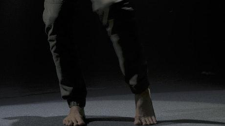 Man dancing barefoot in the dark