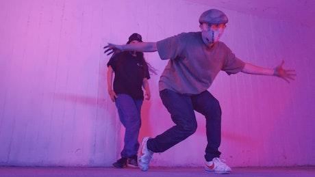 Man dancing break dance with a girl behind