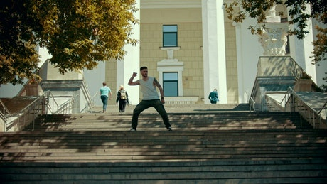 Man dancing on some stairs in the street