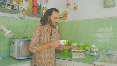 Man dancing while drinking coffee in an 80s kitchen