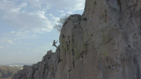 Man descending with rope from the top of a mountain