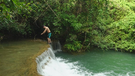 Man dives into a small waterfall