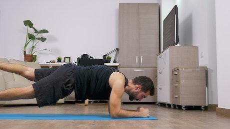 Man does full body yoga exercise in living room