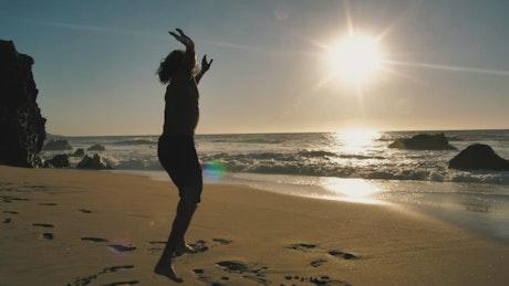 Man doing a cartwheel on the beach