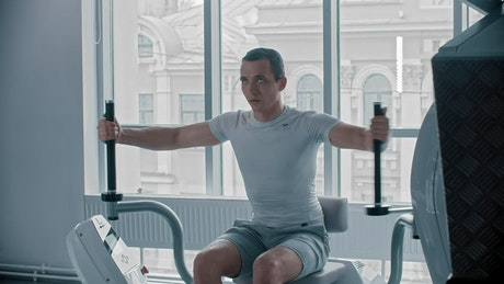 Man doing chest exercise at a white gym